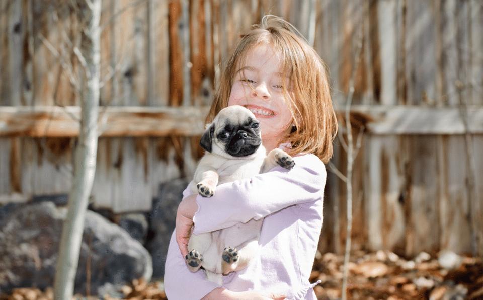 Fetiță ținând un pui de cățel în brațe.